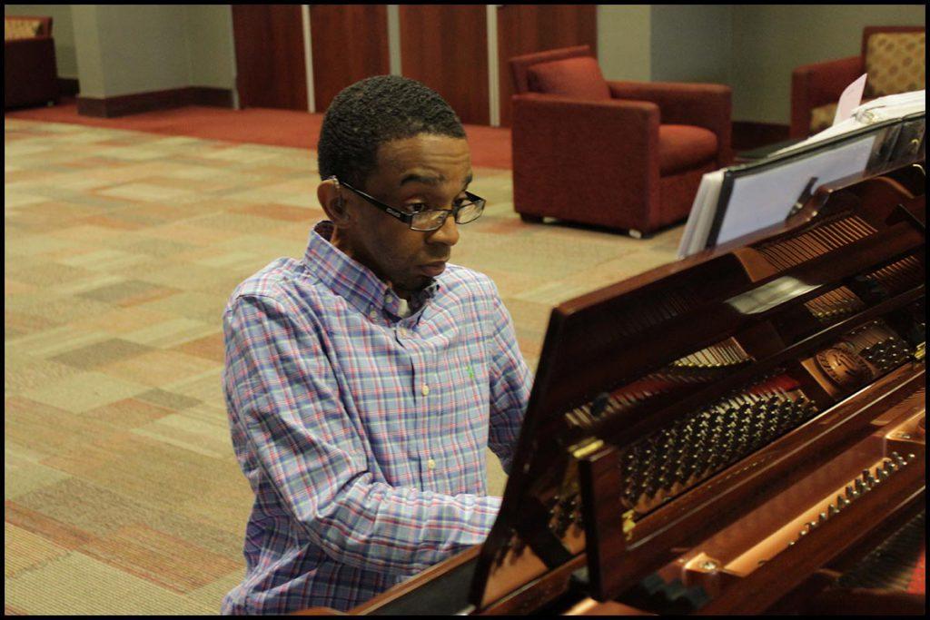 Keyone Docher practicing piano in a plaid shirt